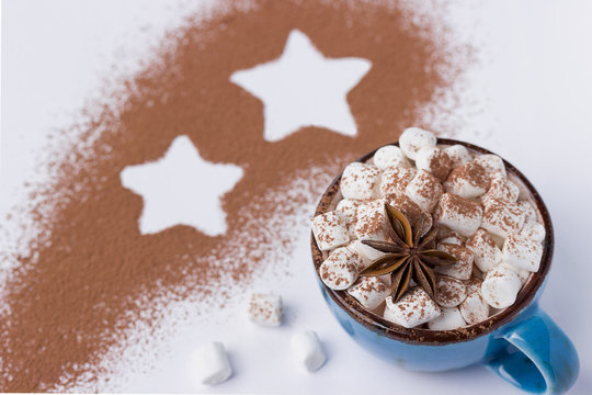 Blue cup with marshmellow cacao powder and star.