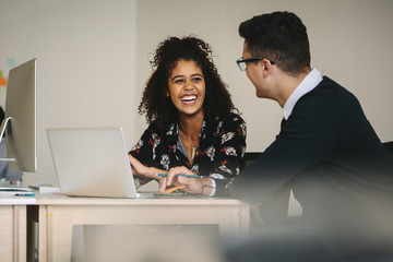 Smiling businesswoman discussing work with colleague in office