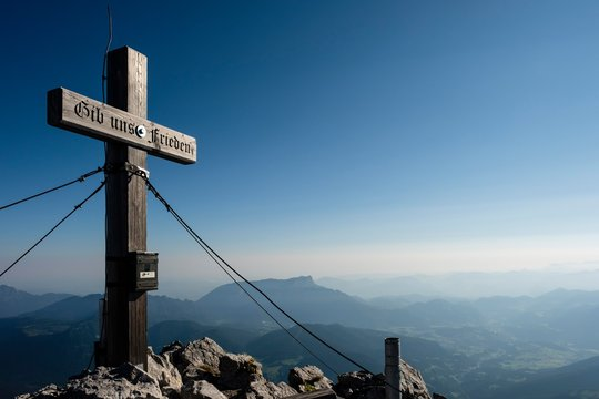 Summit cross of the Hochkalter, 2.607m, behind the Untersberg, Berchtesgaden Alps, Ramsau, Berchtesgaden National Park, Berchtesgadener Land, Bavaria, Germany, Europe