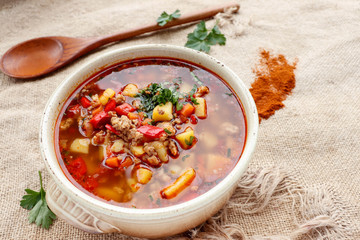 Bulgarian potato soup with paprika and minced meat in a ceramic bowl