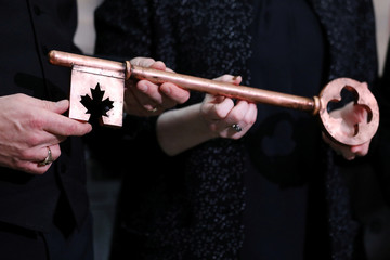 Canada's Public Services Minister Qualtrough presents House of Commons Speaker Regan with a ceremonial key during an event in Ottawa