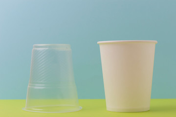 Inverted plastic cup and an environmentally friendly paper disposable cup for drinking water and hot drinks on a colored background. Concept no more plastic!