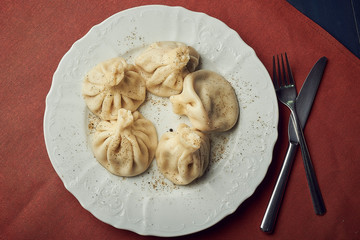 Traditional chinese or asian food, steamed dumpling served on white plate with fork and knife