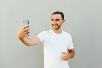 Happy young man making selfie isolated on gray background