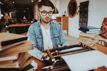 Text Writer Working on Typewriter Sits at Desk