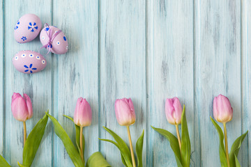 Row of bright pink tulips on blue wooden background and colored easter eggs, top view