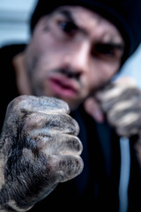 Aggressive fighter or boxer punching.  Sports, crime, aggression concept.  Selective focus on the fist.