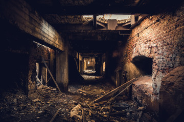 Dark corridor in ruined abandoned brick factory interior, creepy way to freedom and horror concept