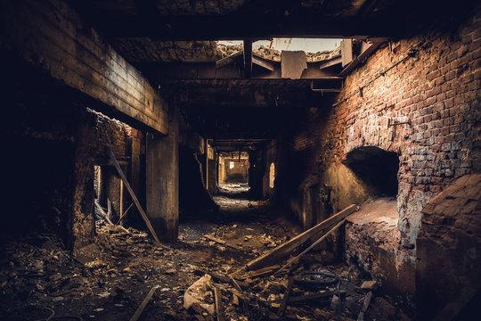 Dark corridor in ruined abandoned brick factory interior, creepy way to freedom and horror concept