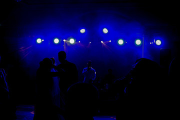 Blue light shine over dancing people in the darkness in front of a stage with a band and a singer on it