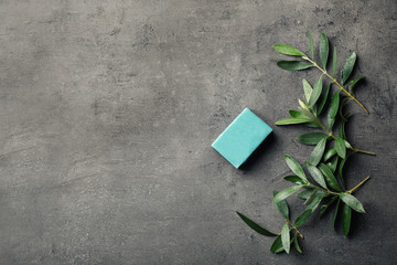 Handmade soap bar and olive leaves on grey background, top view with space for text