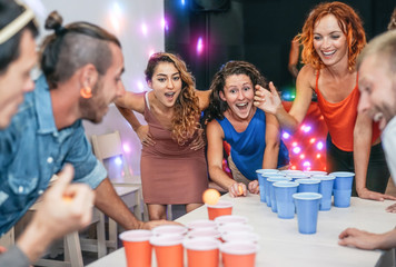 Group of happy friends playing beer pong in pub cocktail bar - Young millennials people having fun doing party alcohol games at night - Friendship and youth lifestyle nightlife concept