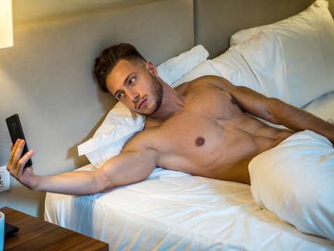 Attractive young man using cell phone to take selfie photo and send it, while laying on bed, shirtless