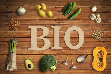 Wort BIO und verschiedene Gemüse auf Holzhintergrund