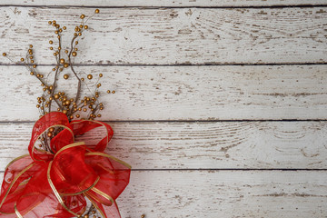 red bow and twigs on white weathered wood background