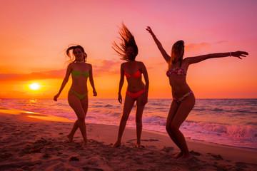 tres chicas disfrutando y riendo al atardecer en una playa paradisiaca.