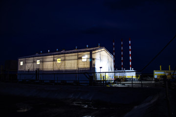 large industrial hangar illuminated from the inside on the construction site in the night