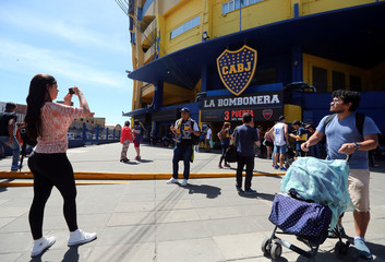 A man poses for a photo in front of Boca Juniors' La Bombonera stadium in Buenos Aires