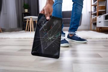 Man Picking Up Damaged Tablet