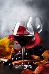 Dry red wine in large glass, autumn still life with red and yellow leaves on gray background, wine tasting, selective focus