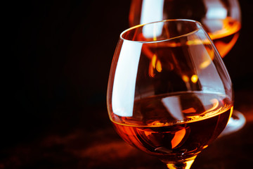 Grape brandy in shot glass, dark brown background, selective focus