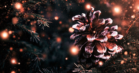 Christmas or New Year blurred snow background with festive fir tree and pine cones, selective focus