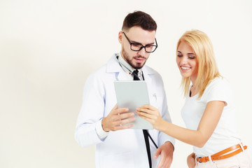 Male doctor and female patient looks at tablet computer for health data record. Healthcare and medical service.