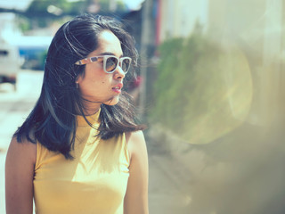 Happy Asian woman wearing sunglasses with sun light outdoor, lifestyle concept.  Reflection effect.