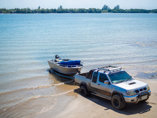 Motor boat being pulled with the pickup truck trailer on the beach