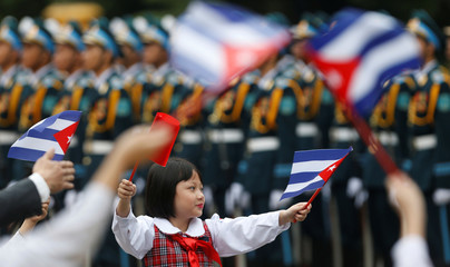 A Vietnamese school girl waves Vietnamese and Cuban flags upon arrival of Cuba's President Miguel Diaz-Canel (not pictured) before a welcoming ceremony at the Presidential Palace in Hanoi