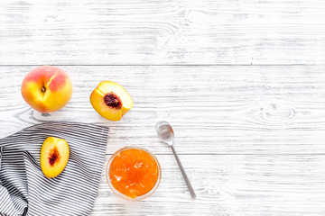 Fruit dessert. Peach jam in jar near slices of fresh peaches and spoon on white wooden background top view copy space