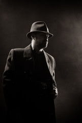 man in a black hat and coat on a dark background, Studio photo
