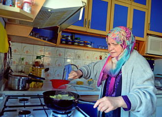 An elderly rural woman is frying potatoes in the kitchen in a small town of Turkey. Old Turkish muslim woman.