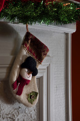 close up view of  christmas wool sock is hanging on fireplace top