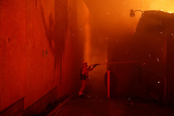 Firefighters battle to save structures while battling the Camp Fire in Paradise