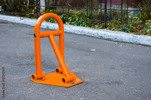 orange parking barrier on the asphalt  orange parking bay