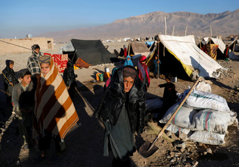 Internally displaced Afghan boys stand outside their tent at a refugee camp in Herat province