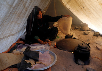 An internally displaced Afghan woman cooks bread at a refugee camp in Herat province