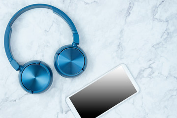 Blue headphone for music and smart phone with mock up on a marble background.