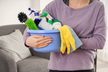 Woman with basin full of cleaning supplies at home, closeup