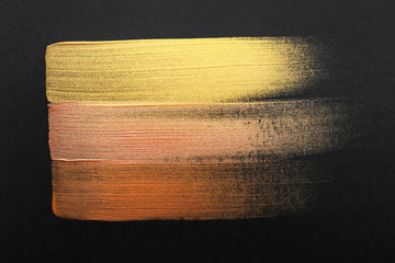 Strokes of different gold paints on dark background