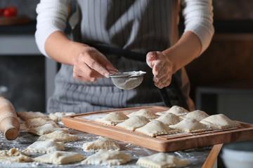 Woman making tasty ravioli on table
