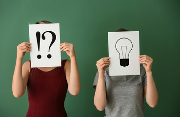 Women holding sheets of paper with exclamation and interrogation marks and drawing of light bulb on color background