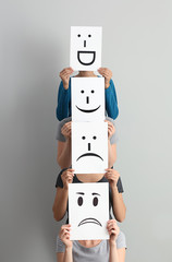 Young women hiding faces behind sheets of paper with drawn emoticons on light background