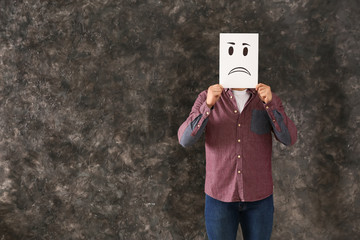 Man hiding face behind sheet of paper with drawn emoticon on grey background