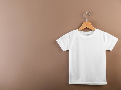 Hanger with blank white t-shirt on color background