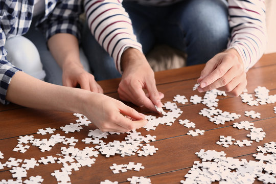 Young couple doing jigsaw puzzle at home, closeup