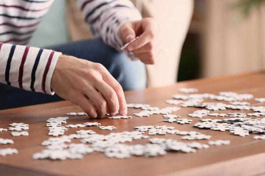 Young man doing jigsaw puzzle at home, closeup