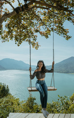 asian woman portrait on a swing with beautiful nature background