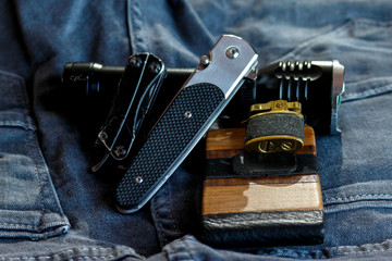 Every day carry equipment items close up. Pocket knives, multi tools, flashlight, card holder and wallet on jeans.